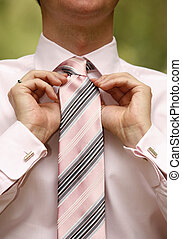 Man tying necktie - Young man wearing suit adjusting tie