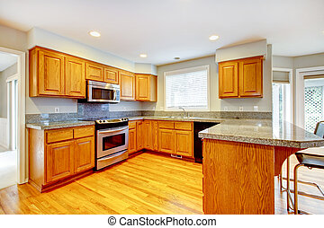 New classic wood large kitchen with grey countertop.