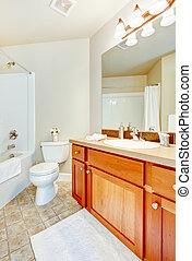 Bathroom with white tub, toilet and sink and wood cabinets.