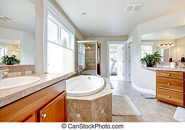 Large bathroom with tub , double sinks and wood cabients.