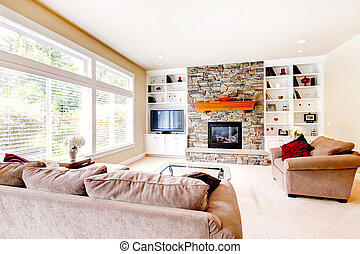 Large bright living room with fireplace and beige sofas.