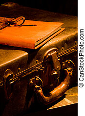 old, vintage, antique leather suitcase with leather bound and tied book on top painted with warm light