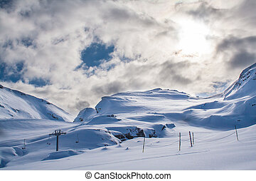 Ski lift in Alps - Snowy mountain with huge white cloud...