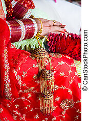 Indian wedding - Bride is sitting in red wedding dress and...