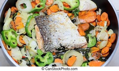 salmon cooking - fresh salmon fillet with vegetables in the...
