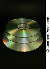 CDs/DVDs - Three CDs or DVDs against a black background