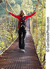 Woman hiking in suspension bridge with outstretched to hands...