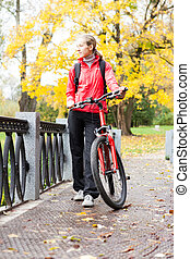 Woman cyclist with bike in autumn park
