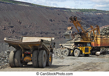 Opencast mining - Trucks being loaded with iron ore on the...