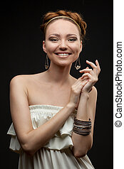 portrait of smiling beautiful young woman on black
