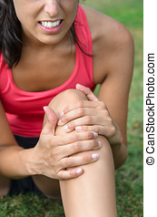 Knee sport injury - A young woman in pain because of a knee...
