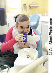 Girl rinsing mouth at dentist - Cute happy girl rinsing...