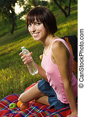 Lovely girl on picnic with bottle of fresh mineral water