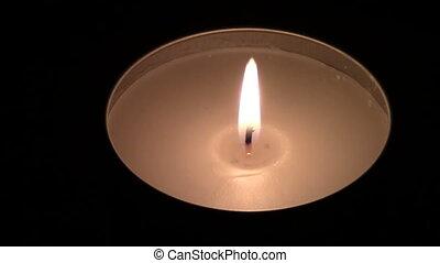 Candle burning on dark background