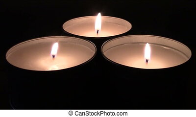 Candles burning on dark background