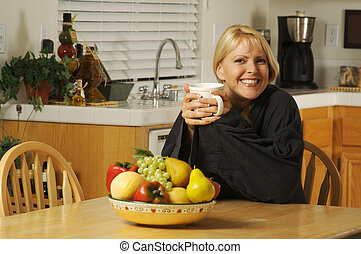 Woman In Kitchen with Cup of Coffee - Beautiful, young woman...