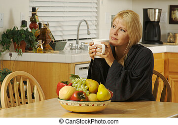 Woman in Kitchen with Cup of Coffee