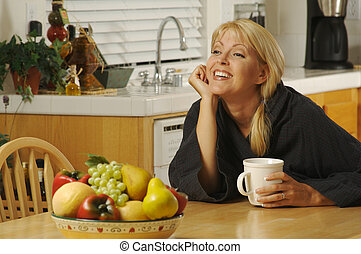 Woman with Cup of Coffee in Kitchen Smiling