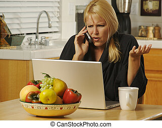 Woman Cell Phone & Laptop - Woman in her kitchen on cell...
