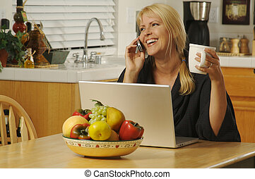 Woman in Kitchen on Cell Phone & Laptop - Woman smiling, in...