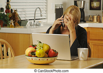 Cell Phone Stress, Laptop - Woman in her kitchen on cell...