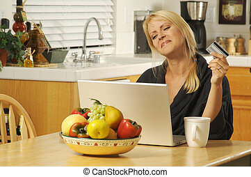 Using Laptop E-commerce - Woman holding credit card in her...