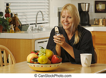 Woman In Kitchen Using Cell Phone