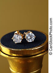 gold earrings stud  with diamonds  on gold background
