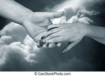 Trust - Man\\\'s and female hand on a background of the sky