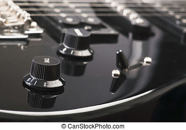controls and cords, of a black electric guitar