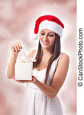 Attractive woman is opening a gift - beautiful woman is...