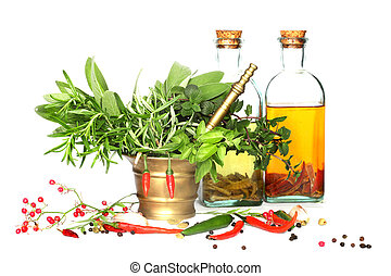 Mixed herbs of sage, rosemary, basil with red hot peper in mortar with pestle  botle of oil on white background