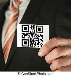 concept with qr code - businessman holding a card with qr...