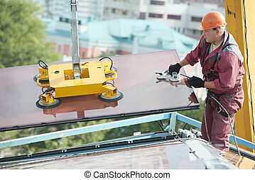 builder joiner installing glass window on building - worker...