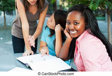 Student smiling at camera - Young lady smiling at camera...