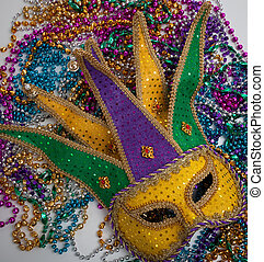 A yellow Mardi Gras mask and beads