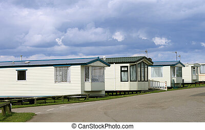 Row of caravan trailersin holiday park with cloudscape...