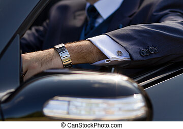 Hand of businessman in cabrio - Posh cufflinks on his shirt,...