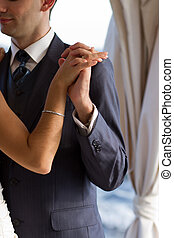 Couple dancing the wedding dance - Hands of newlyweds...