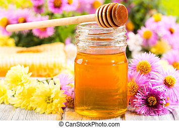 jar of honey with different flowers