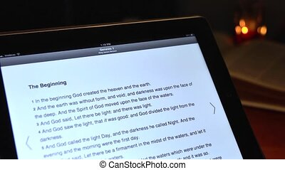 The Holy Bible on a tablet computer - Bible text scrolls on...