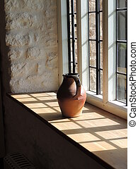 Windowsill - Earthern pot on a sunlit windowsill
