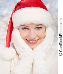 beauty happy girl in Christmas hat and mittens on the winter...