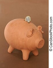 Putting coin into the piggy bank.