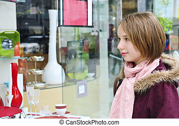 Teenage girl shopping - Teenage girl window shopping on city...