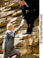 Climbing - Image of helpful man holding businesswoman by...