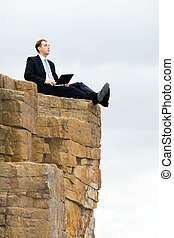 Sitting on the rocks - Vertical photo of man in suit sitting...