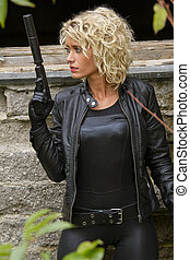 Woman in leather with silencer gun