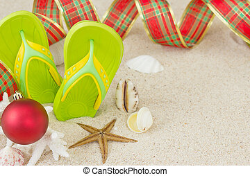 Flip Flops in the sand with shells and Christmas decoration....