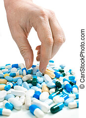 Taking medicine - hand taking pills from the heap of...